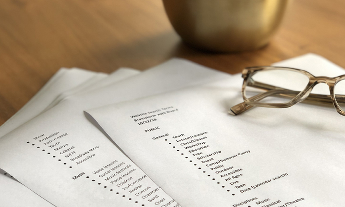 papers with list of categories printed and pair of glasses on top